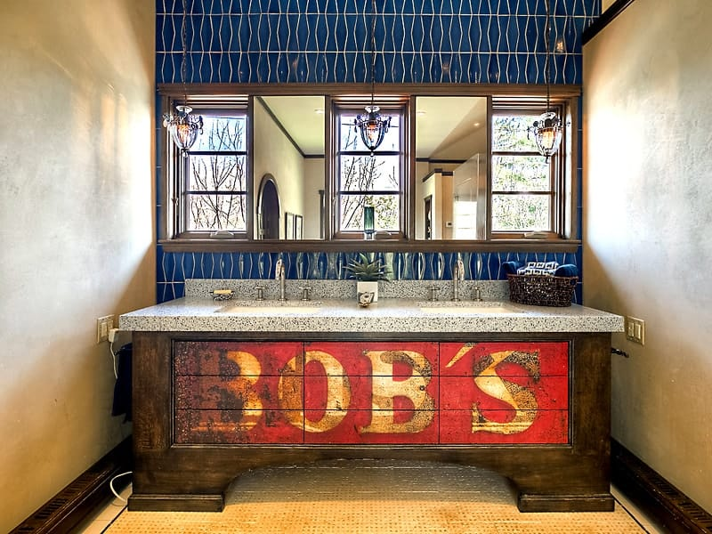 The sink of this bathroom has a wooden antique vanity with its original logo paint still on it. Images courtesy of Toptenrealestatedeals.com.