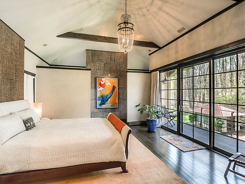 The primary bedroom has a wide floor space fitted with dark hardwood flooring brightened by the large sliding glass doors across from the wooden sleigh bed. Images courtesy of Toptenrealestatedeals.com.