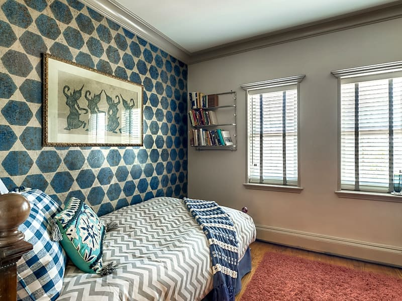 This simple bedroom has patterned wallpaper adorned with a wall-mounted artwork above the bed that was placed against the wall next to a red area rug of the hardwood flooring. Images courtesy of Toptenrealestatedeals.com.