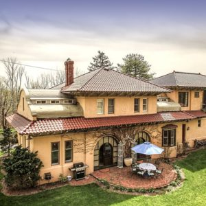 The beautiful train station that was turned into a private home has gorgeous beige exterior walls and clay tile roof that matches the terracotta flooring of the outdoor area beyond the elegant arches. Images courtesy of Toptenrealestatedeals.com.