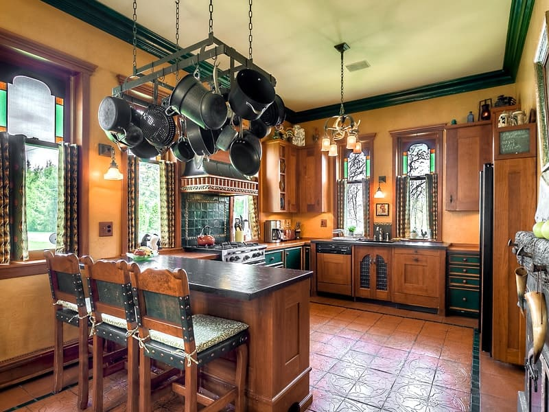This is a gorgeous and homey kitchen with a U-shaped peninsula that has wooden cabinetry topped by a pan rack hanging from the ceiling. Images courtesy of Toptenrealestatedeals.com.