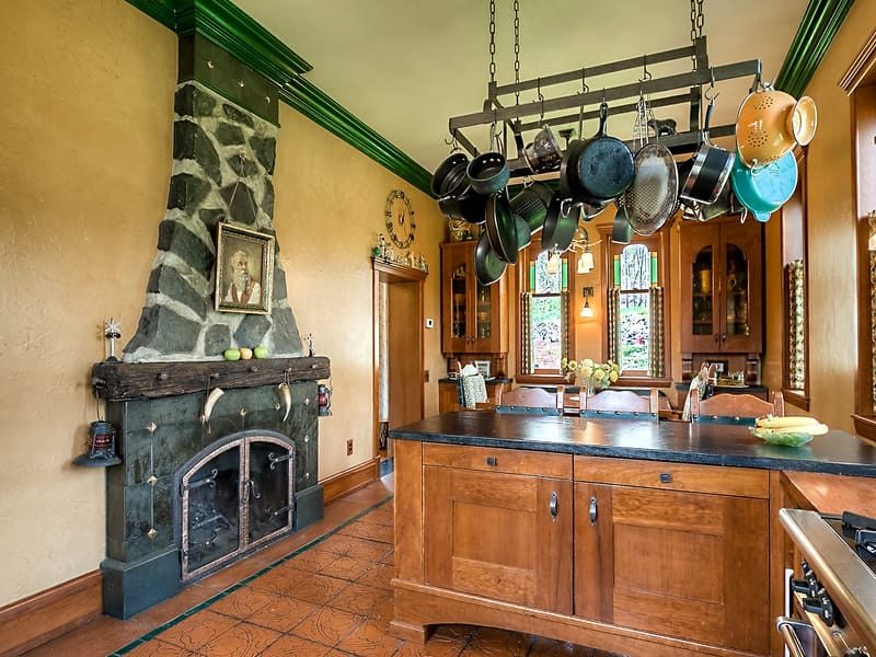 This charming kitchen has its own stone fireplace that stands out against the beige walls and ceiling adorned with green moldings. The fireplace matches well with the terracotta flooring tiles. Images courtesy of Toptenrealestatedeals.com.