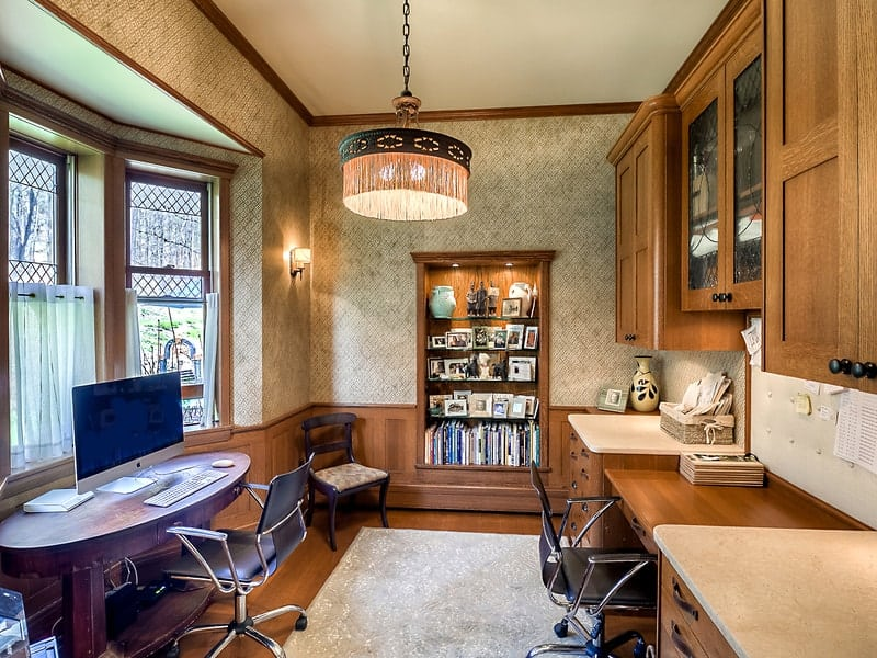 This is home office with a couple of work areas on either side of the room. One has a built-in wooden desk with floating cabinets above and on the other is a small station by the window. Images courtesy of Toptenrealestatedeals.com.