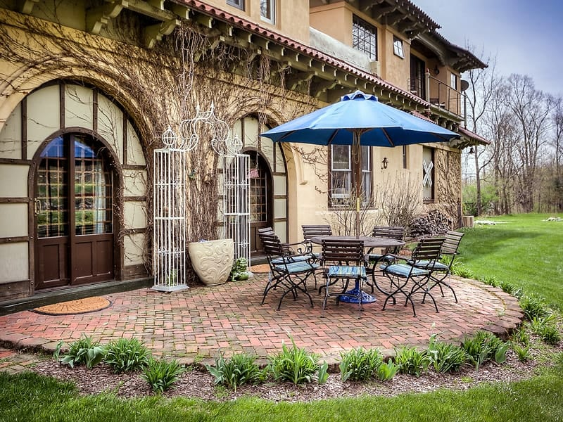 This beautiful outdoor dining area is just beyond the gorgeous arches of the house. It has an outdoor metal dining set under a big umbrella on a terracotta brick flooring. Images courtesy of Toptenrealestatedeals.com.