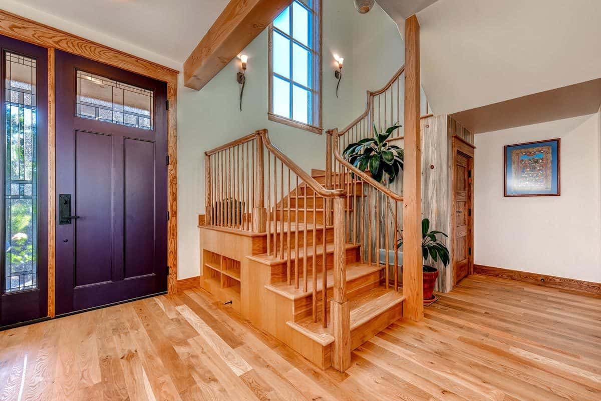 Front entry door with glass panels sitting next to the wooden staircase lit by wall sconces.