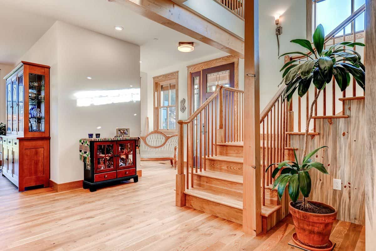 Foyer with a display cabinet over the light hardwood flooring matching with the staircase.