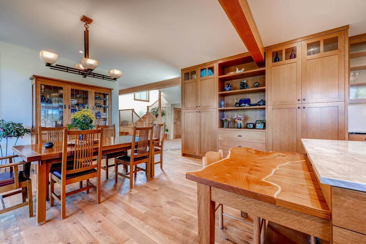 Dining area beside the kitchen with a rich wooden dining table under a warm chandelier.
