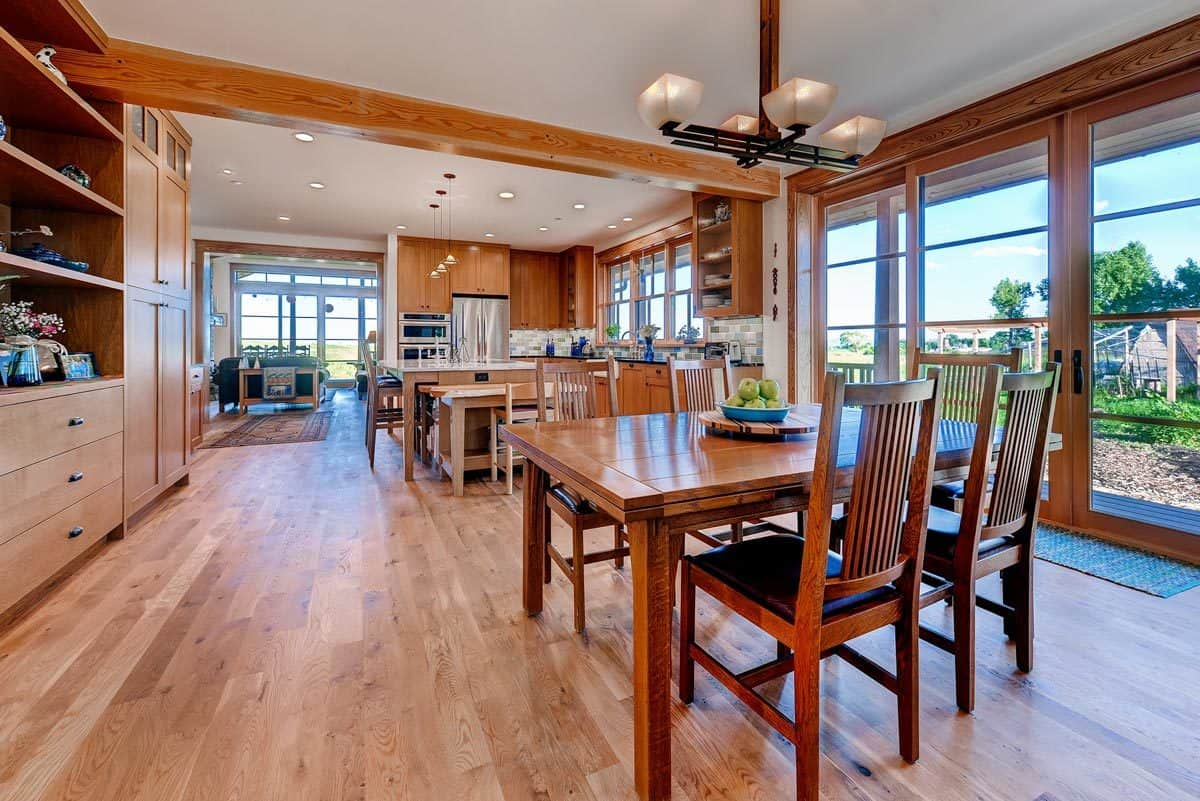 Combined dining and kitchen with hardwood flooring and a french door leading out to the porch.