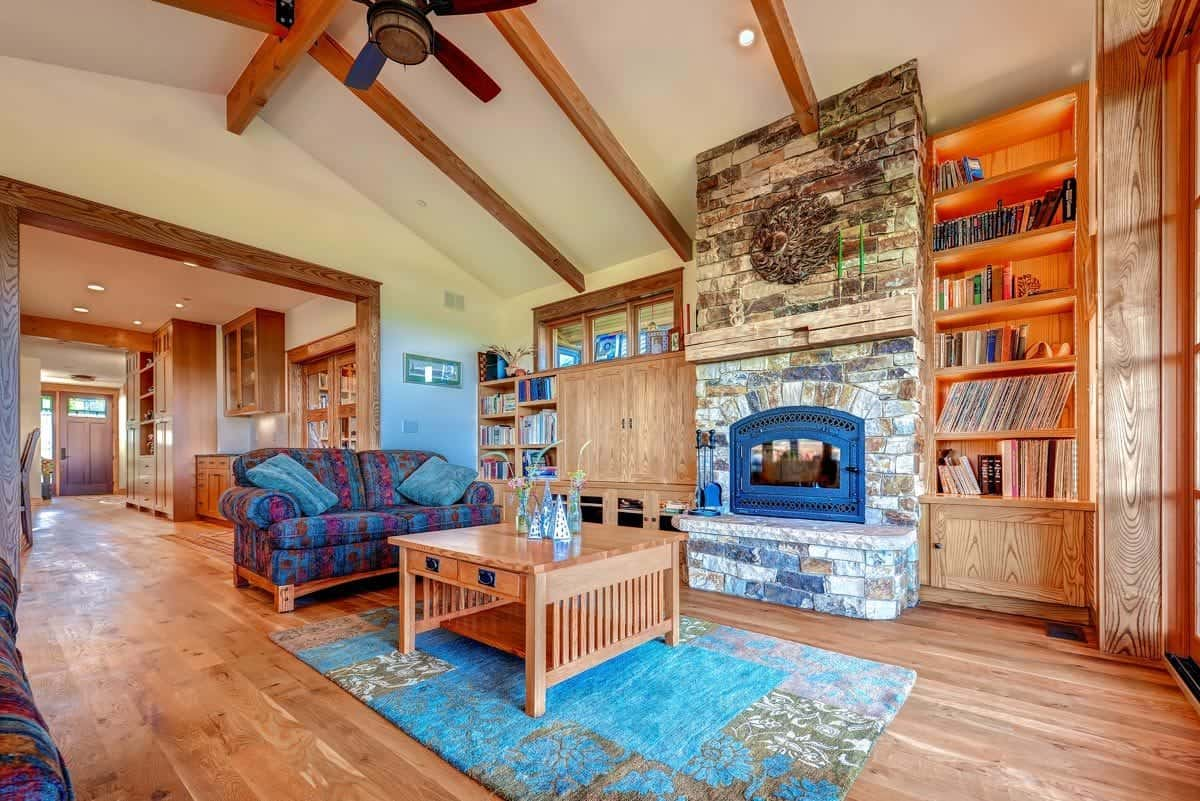 Living room with a stone brick fireplace, patterned sofas and a wooden coffee table sitting over a blue printed rug.