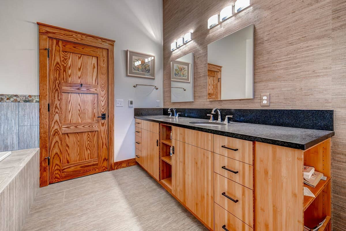 The primary bathroom features a dual sink vanity fixed against the wood-paneled wall.