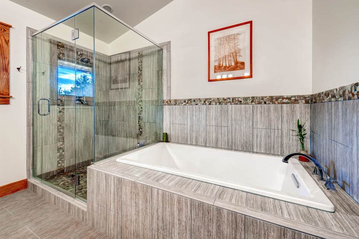 The opposite side of the primary bathroom shows the walk-in shower and deep soaking tub under the red-framed artwork.
