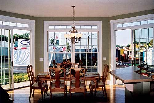 Dining area with cushioned chairs and a wooden dining table illuminated by a glass chandelier.