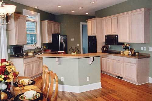 The kitchen offers black appliances, white cabinetry, and wooden top island bar matching with the sage green walls.