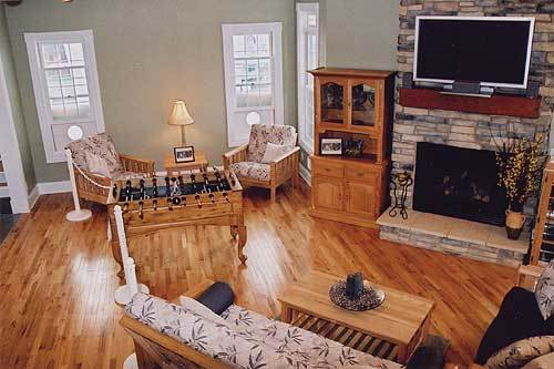 The living room has cushioned seats, a wall-mounted TV, a stone fireplace, and a wooden cabinet blending in with the hardwood flooring.