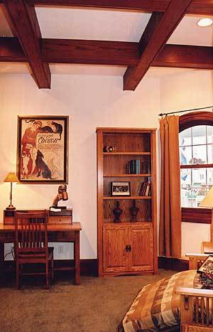 The home office has a coffered ceiling, wooden furnishings, and an arched window that lets natural light in.