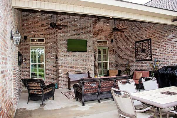 A closer look at the rear patio shows the metal dining set and wicker chairs facing the wall-mounted TV that's fixed against the brick wall.