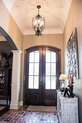 The foyer has a wooden french front door, an ornate pendant and a distressed console table under the decorative artwork.