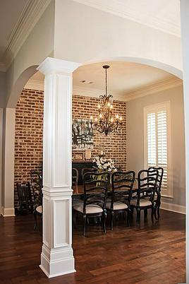 A formal dining room framed with open arches offers a dark wood dining set illuminated by a warm chandelier.