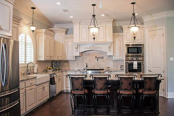 This kitchen is equipped with stainless steel appliances, a farmhouse sink and a center island bar complemented by metal counter chairs and glass pendants.