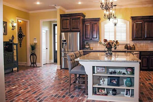 This kitchen area has brick flooring and yellow walls lined with white crown molding.