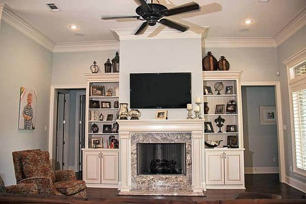 The marble fireplace and TV are flanked by white built-ins filled with various decors.