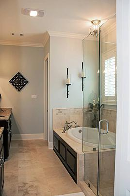 Primary bathroom with dual sink vanities, a corner tub, and a walk-in shower enclosed in frameless glass.