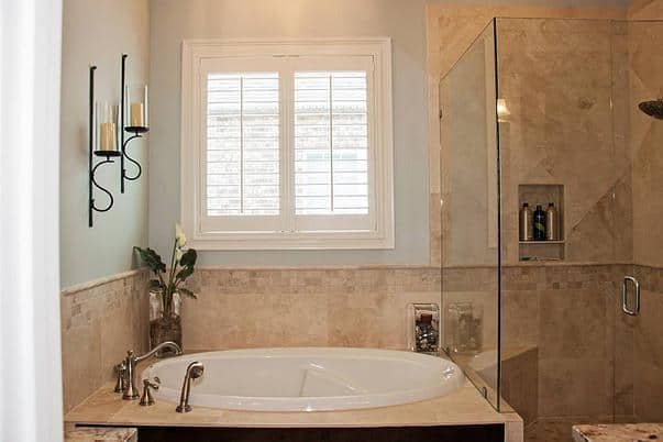 A closer look at the walk-in shower and deep soaking tub lit by candle sconces.