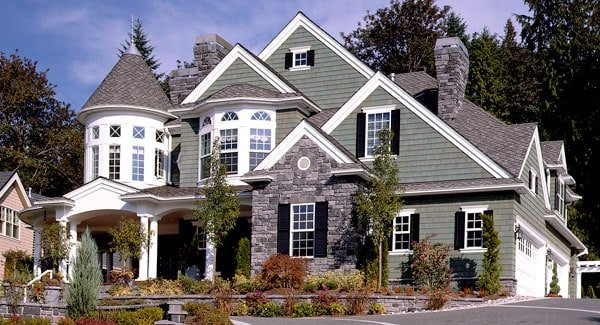 Home's facade with brick cladding, stone accents, turrets, and covered porch framed with archways.