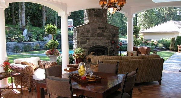 A closer look at the covered porch with wicker seats, a wooden dining set, and a stone fireplace that serves as a focal point in the area.