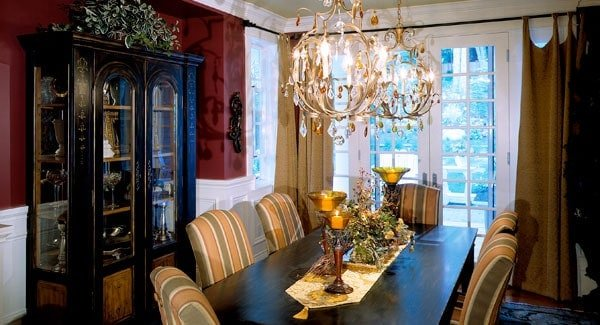 A closer look at the formal dining room shows the black display cabinet and a striped dining set illuminated by gilded chandeliers.