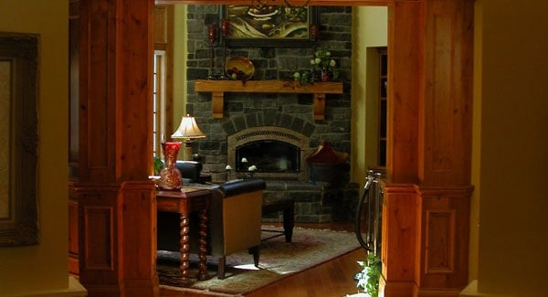 Den with a cozy seat and a stone brick fireplace lined with a wooden mantel.