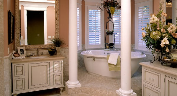 Primary bathroom with sink vanities and a freestanding tub by the bay window lined with interior columns.