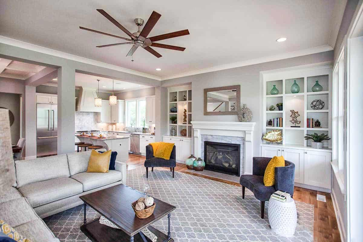 The living room has gray seats, a patterned area rug, and a fireplace flanked by built-ins.
