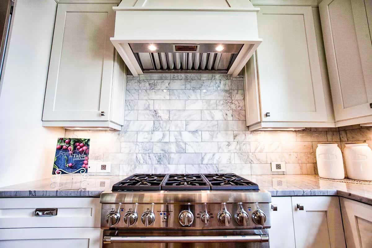 A closer look at the stainless steel cooking range under the bespoke vent hood that's fixed against the marble subway tile backsplash.