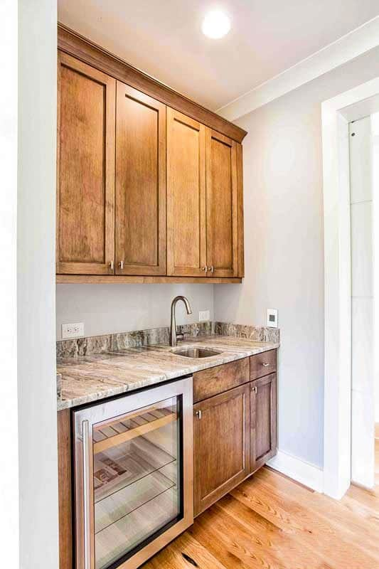 Walk-in pantry filled with wooden cabinets, a beverage fridge, and marble countertop fitted with an undermount sink.