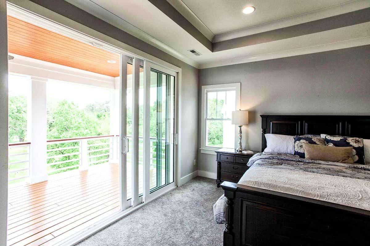 The primary bedroom has gray walls, carpet flooring, tray ceiling and sliding glass doors that lead out to the covered porch.