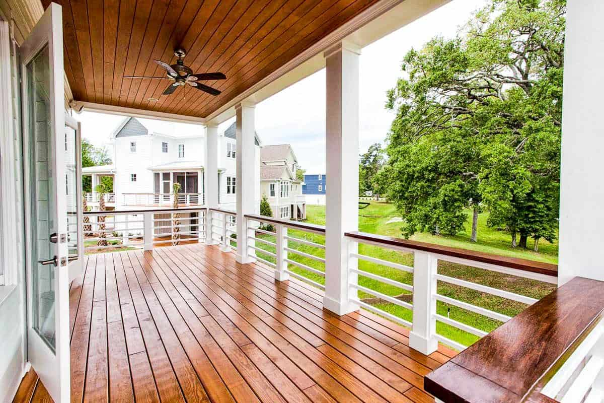 The covered porch has a rich hardwood flooring that matches the paneled ceiling mounted with a fan.