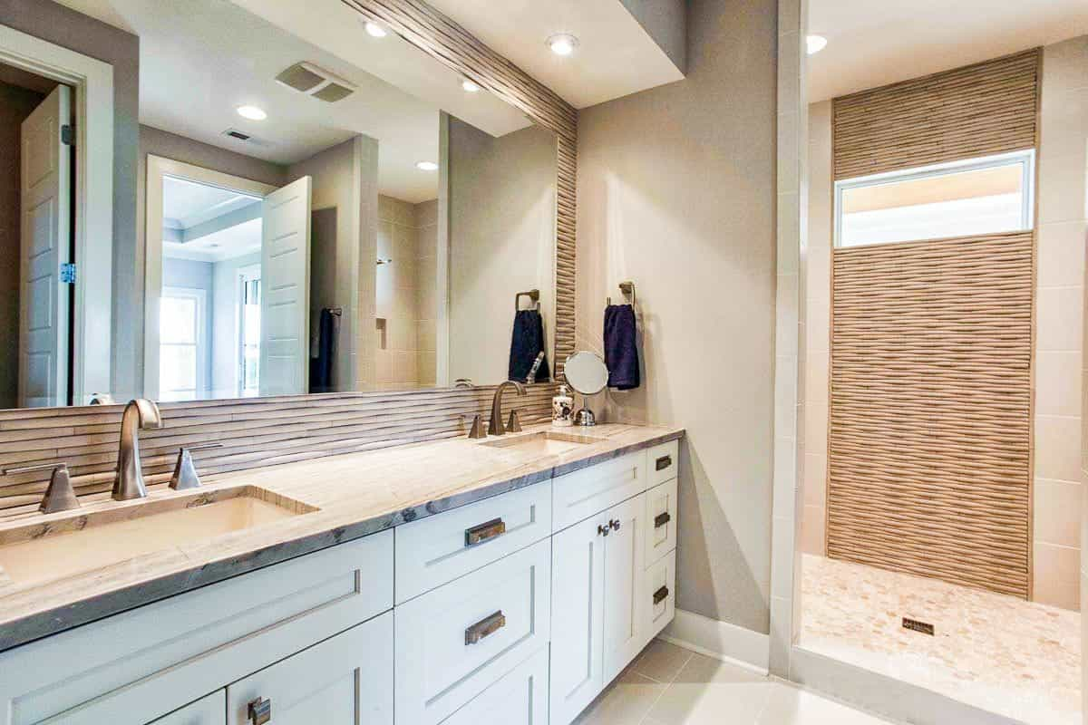 Primary bathroom with a shower area, and dual sink vanity paired with a large frameless mirror.