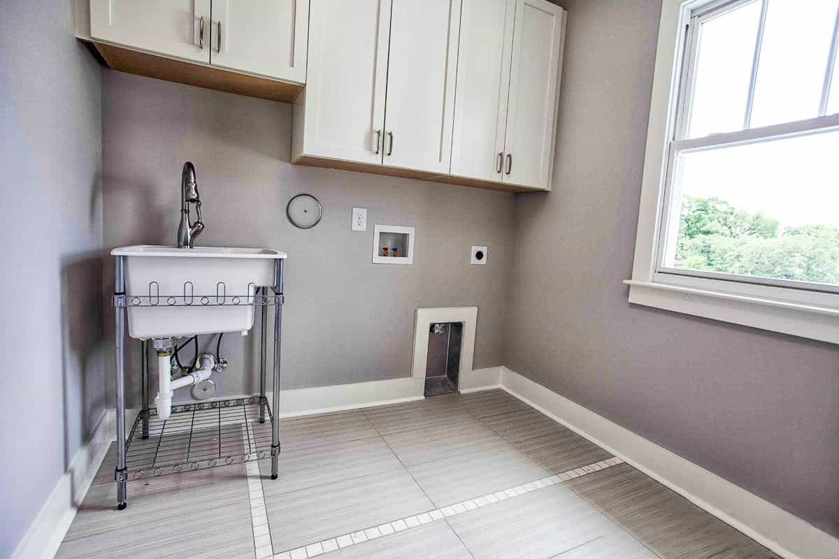 Laundry room with white cabinets, a washstand, and a framed window that brings natural light in.