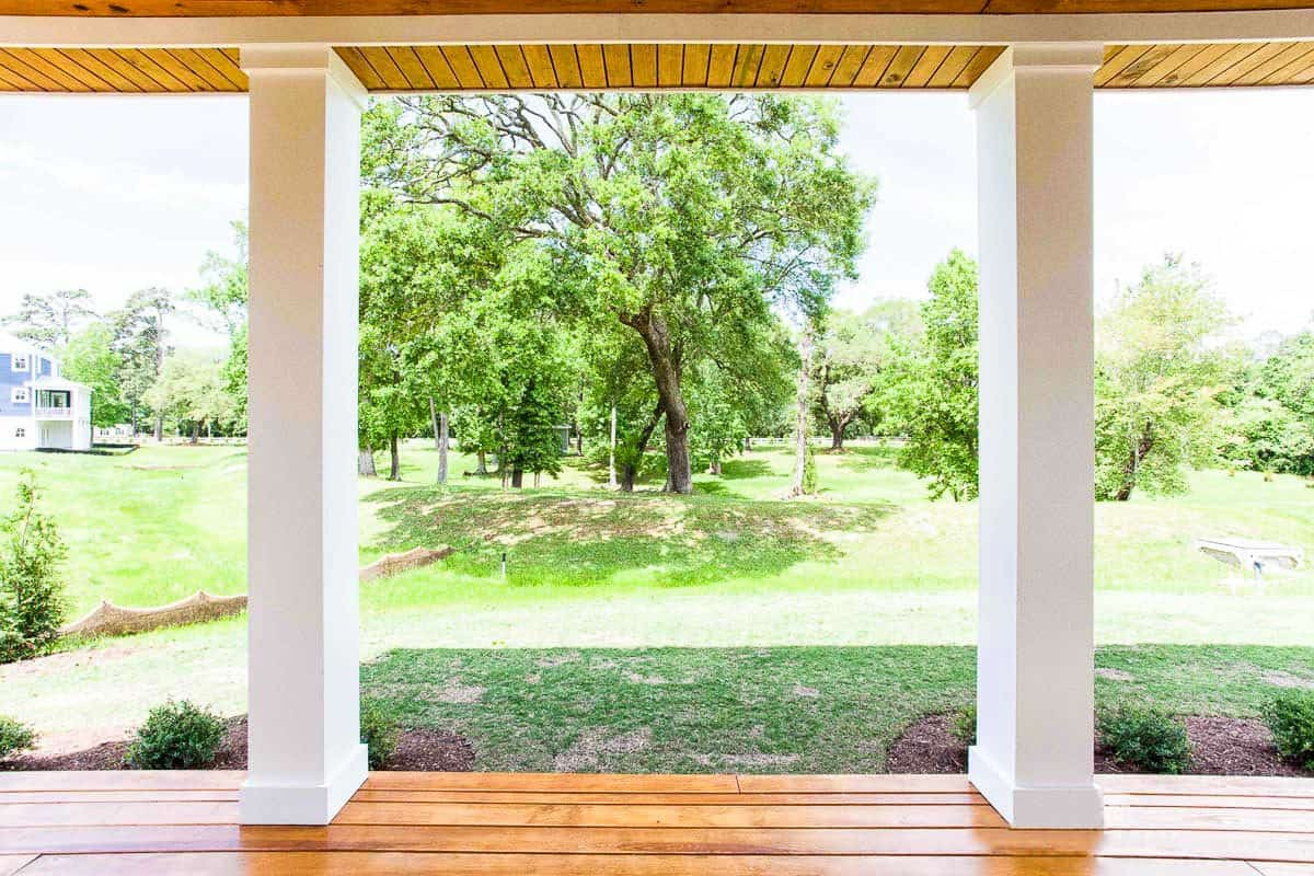 View of the serene lush backyard from the covered porch supported by sleek white columns.