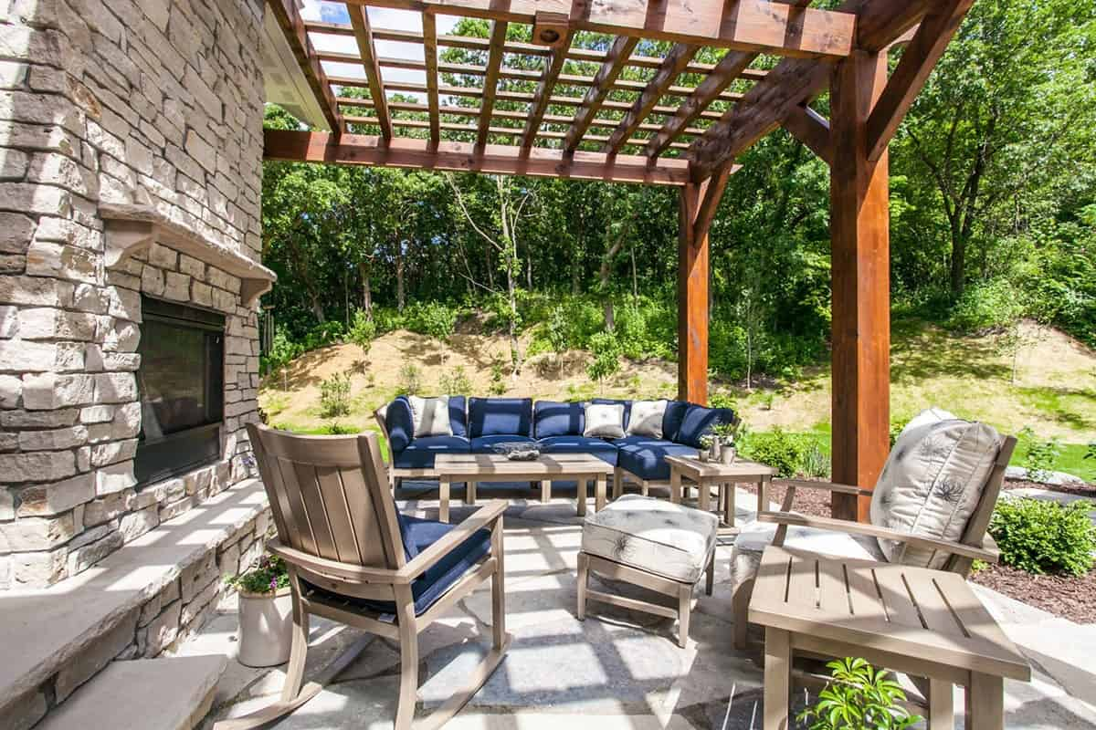 The wooden pergola houses the stone fireplace and light wood seats topped with blue and white cushions.