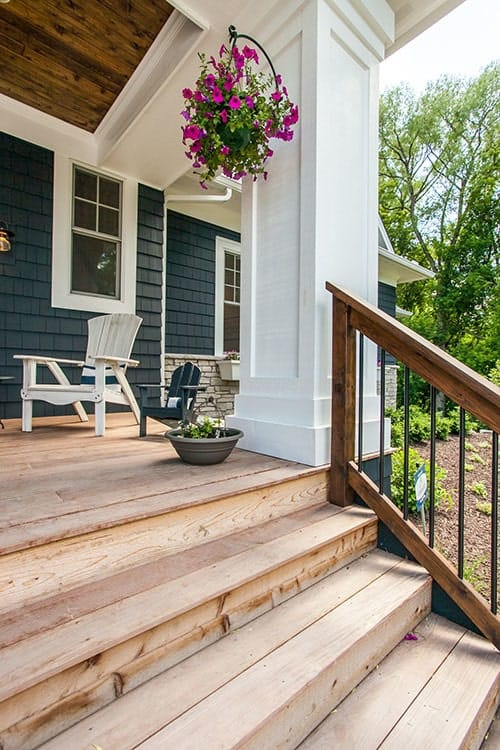 Natural wood staircase with rustic railings leading to the front porch.
