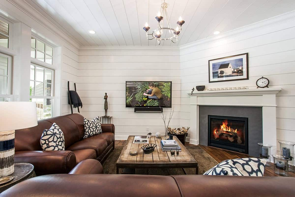 Another view of the living room with elegant leather seats and a corner fireplace fixed against the shiplap walls.