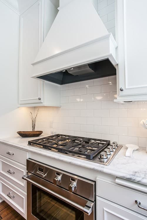 A closer look at the cooking range sandwiched by white drawers. It is paired with a custom vent hood mounted on the white subway tile backsplash.