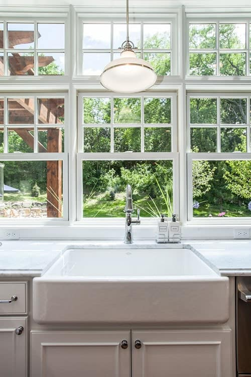 A farmhouse sink is fitted with a gooseneck faucet and lighted by a white pendant.