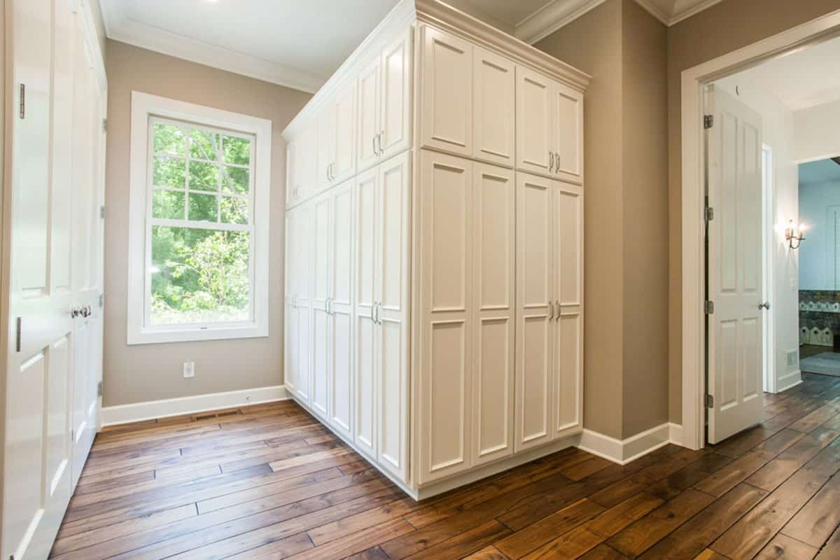 The walk-in closet is filled with white cabinets standing over the dark hardwood flooring.