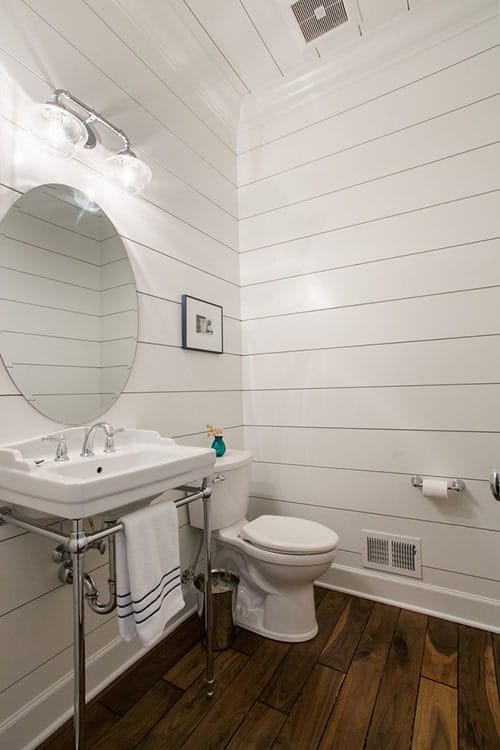 The bathroom has a toilet and a chrome washstand paired with an oval mirror.