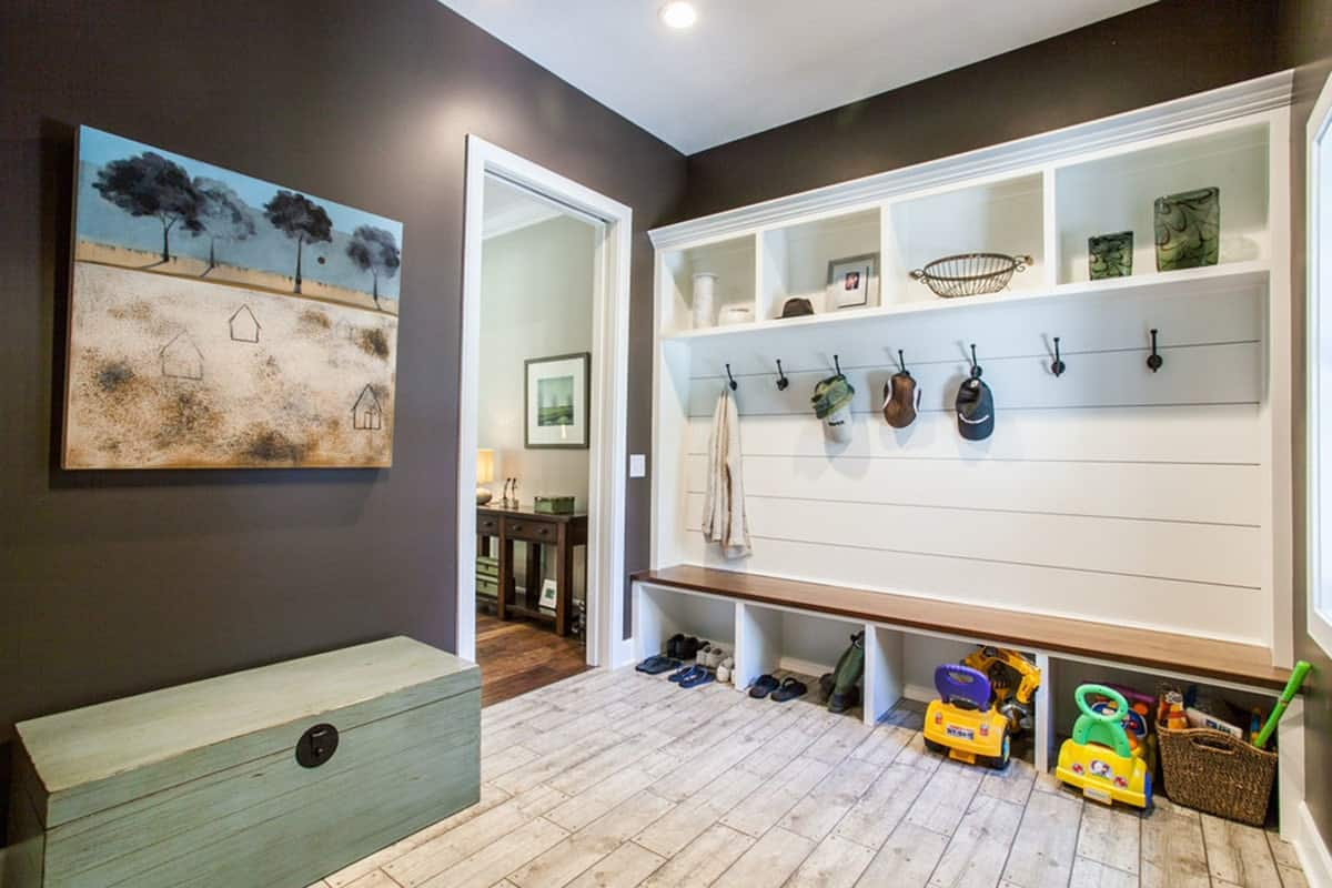 The mudroom showcases a trunk storage along with built-in shelves and bench.