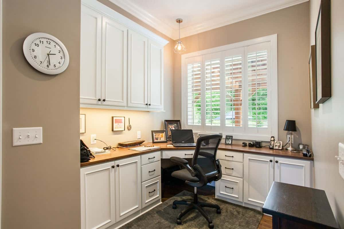 Home office with built-in cabinets and desk complemented by a mesh swivel chair.