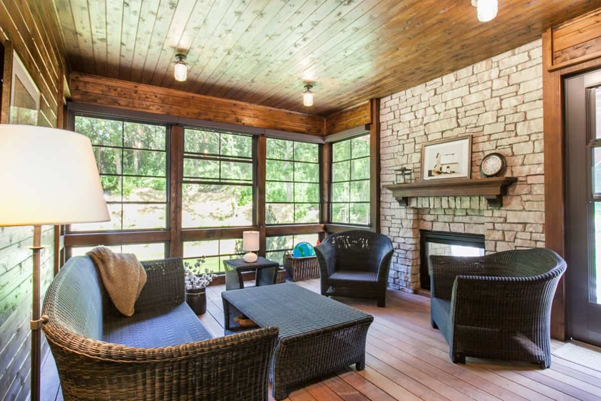 Screened porch with a warm fireplace and wicker seats paired with a matching coffee table.